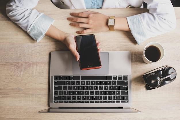 Bovenaanzicht van vrouw hand werken met smartphone en laptop op een houten bureau