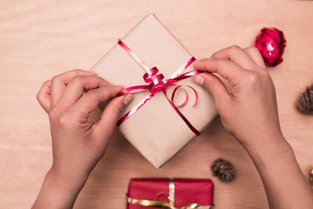 Bovenaanzicht van vrouw handen koppelverkoop rood lint op handgemaakte aanwezig op houten tafel, pakket voor kerstcadeaus.
