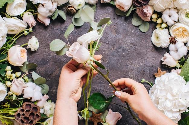 Bovenaanzicht van vrouw handen met bloemen. bloemist maakt stijlvolle bruiloftscompositie, floristisch ontwerp