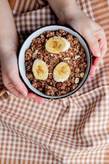 Bovenaanzicht van vrouw handen met kom met noten en bananen op doek oppervlak