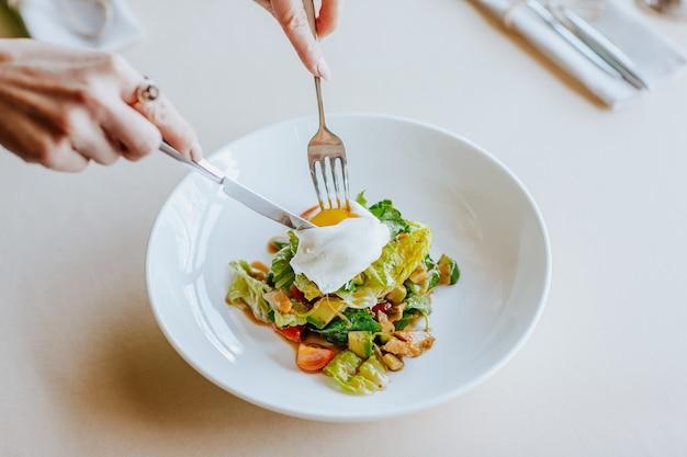 Bovenaanzicht van vrouw handen met mes en vork snijden gepocheerde eiersalade met kipfilet op tafel.