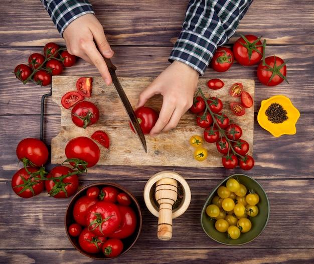 Bovenaanzicht van vrouw handen snijden tomaat op snijplank met mes en zwarte peper knoflook crusher op houten oppervlak