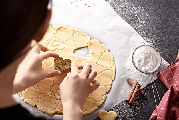 Bovenaanzicht van vrouw harten uit koekjesdeeg op keukentafel met poedersuiker en kaneel snijden