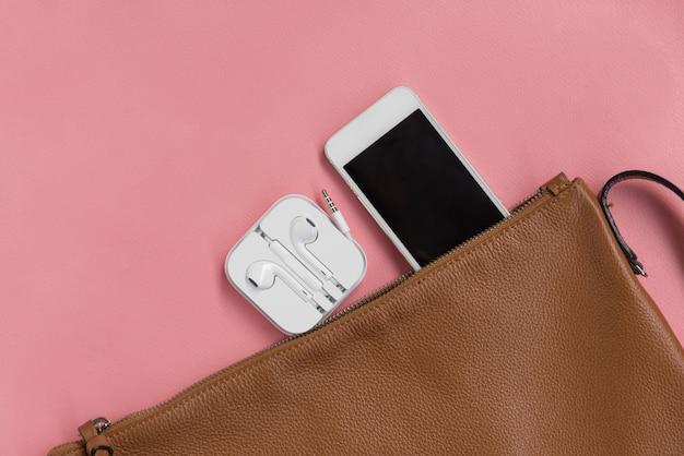 Bovenaanzicht van vrouw hipster travller spullen met slimme telefoon, oortelefoon en lederen tas o