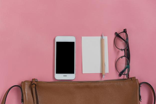 Bovenaanzicht van vrouw hipster travller spullen met telefoon, notitieblok, bril en lederen tas