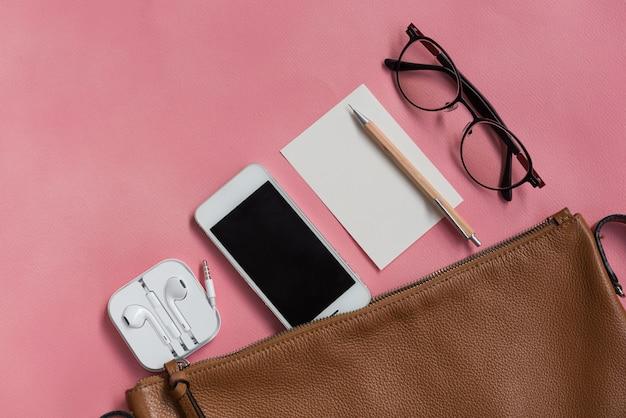 Bovenaanzicht van vrouw hipster travller spullen met telefoon, notitieblok, bril en oortelefoon