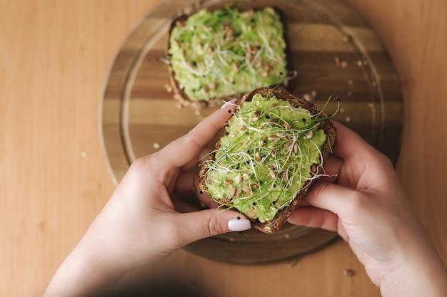 Bovenaanzicht van vrouw houdt rogge toast brood met guacamole bovenop. glutenvrij