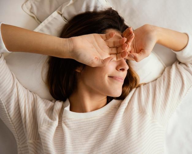 Bovenaanzicht van vrouw in bed thuis wakker