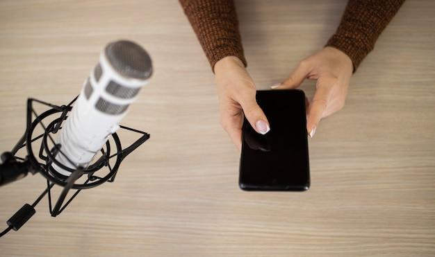 Bovenaanzicht van vrouw in een radiostudio met smartphone en microfoon