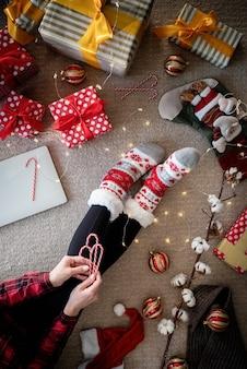 Bovenaanzicht van vrouw in grappige sokken thuis kerstmis vieren