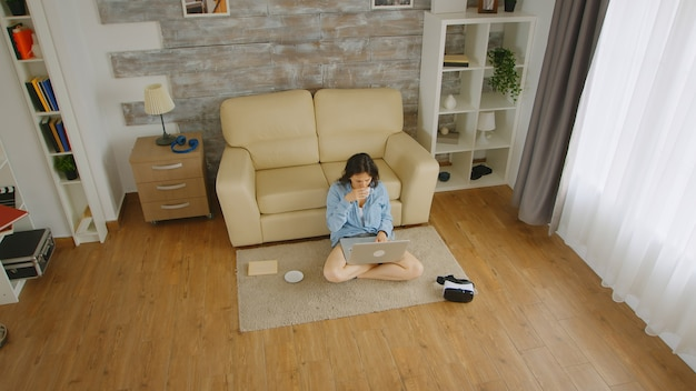 Bovenaanzicht van vrouw in lichte kamer die op een laptop werkt