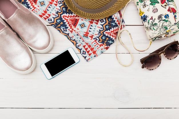 Bovenaanzicht van vrouw kleding, schoenen en accessoires op houten muur