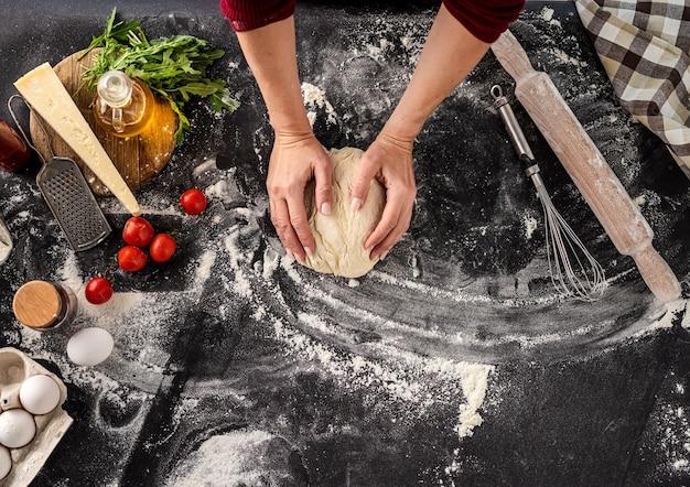 Bovenaanzicht van vrouw kneden van deeg voor pizza bakken op zwarte met bloem bestoven achtergrond