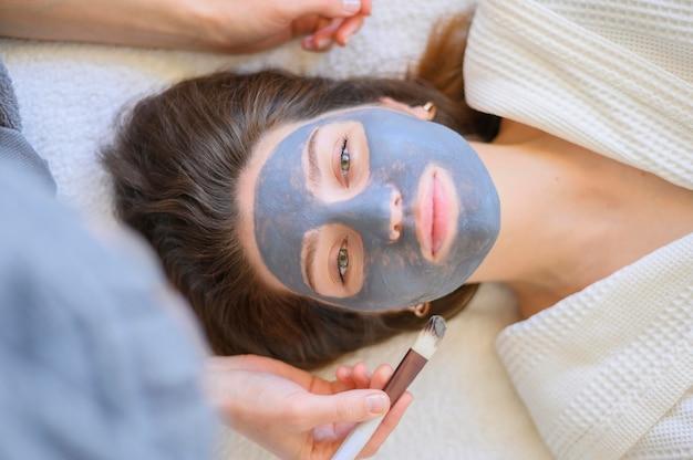 Bovenaanzicht van vrouw krijgt een gezichtsmasker