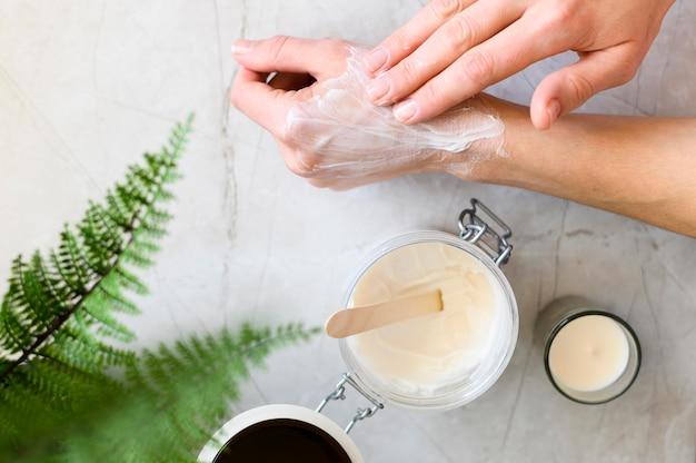 Bovenaanzicht van vrouw met behulp van crème op haar handen