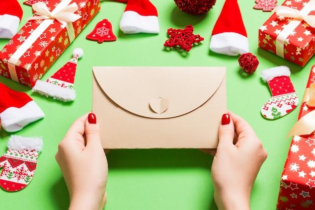 Bovenaanzicht van vrouw met een envelop op groen gemaakt van vakantie decoraties.