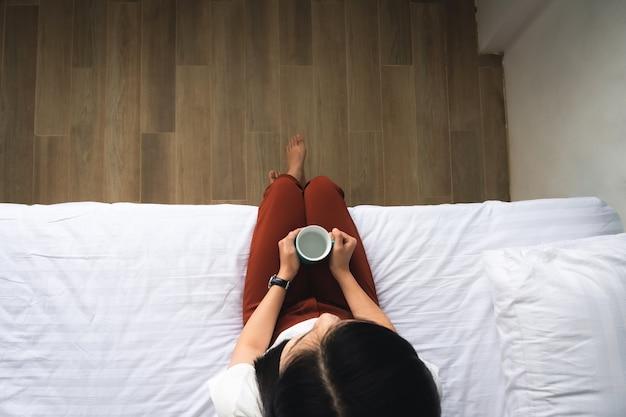 Bovenaanzicht van vrouw met kopje zittend op wit bed ontspannen in de ochtendtijd.