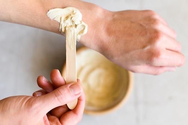 Bovenaanzicht van vrouw met lotion op haar handen