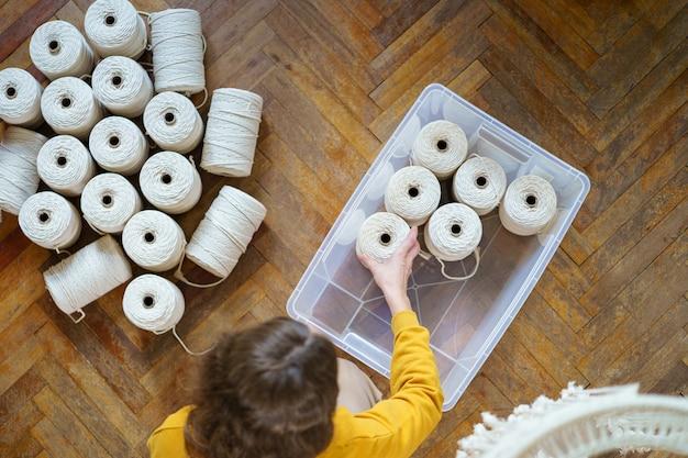 Bovenaanzicht van vrouw met witte macrame katoenen touwen in strengen, zet werkmateriaal in een plastic doos