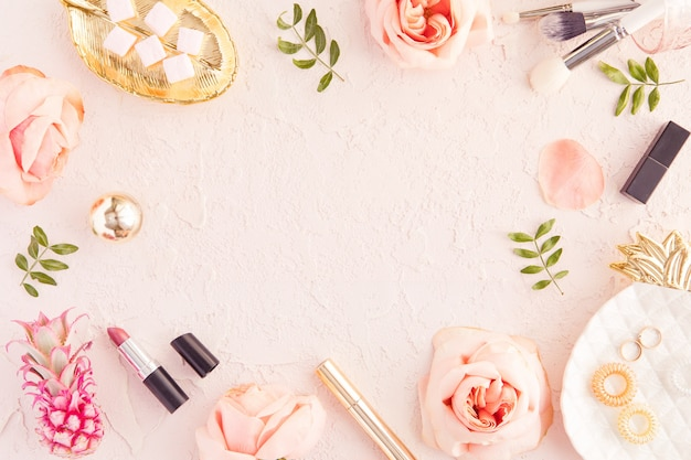 Bovenaanzicht van vrouw schoonheid blogger werkbureau met copyspace, decoratieve cosmetica, bloemen en palmbladen, envelop op roze pastel tafel