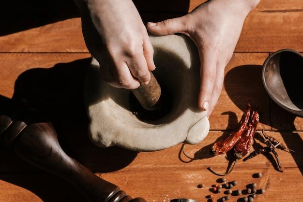 Bovenaanzicht van vrouw slijpen peper