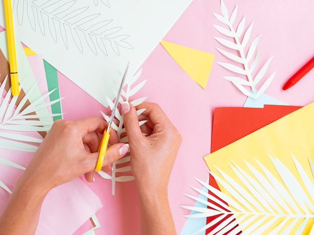 Bovenaanzicht van vrouw snijden papier takken