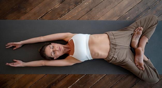 Bovenaanzicht van vrouw thuis beoefenen van yoga