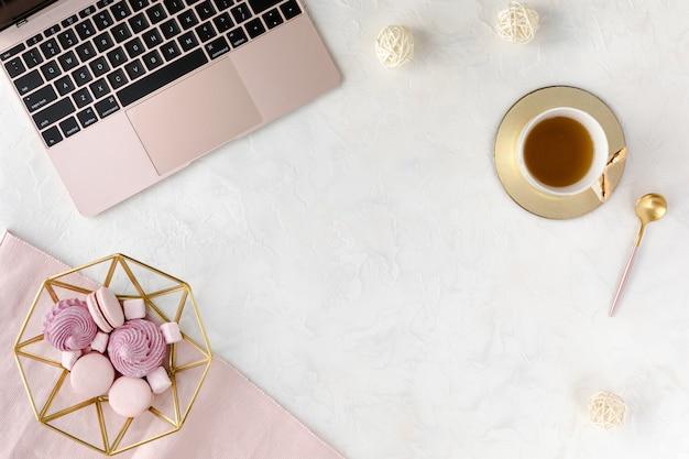 Bovenaanzicht van vrouw zakelijke werkplek met computertoetsenbord, laptop, roze pioen bloemboeket en mobiele telefoon, plat lag.
