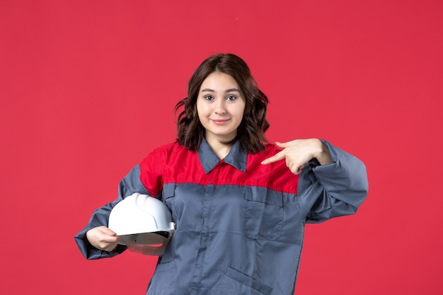 Bovenaanzicht van vrouwelijke architect die een harde hoed vasthoudt en zichzelf wijst op een geïsoleerde rode achtergrond