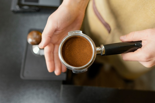 Bovenaanzicht van vrouwelijke barista koffiemachine beker te houden
