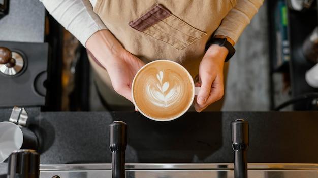 Bovenaanzicht van vrouwelijke barista kopje koffie houden