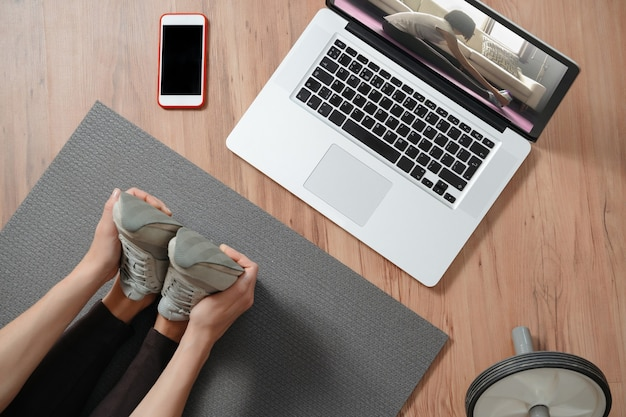 Bovenaanzicht van vrouwelijke benen strekken thuis met behulp van laptop voor online lessen