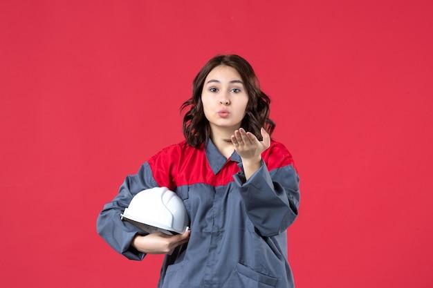 Bovenaanzicht van vrouwelijke bouwer in uniform en met harde hoed die kusgebaar maakt op geïsoleerde rode achtergrond