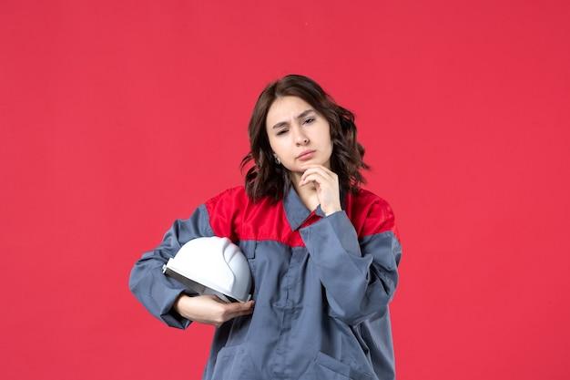 Bovenaanzicht van vrouwelijke bouwer in uniform en met harde hoed diep nadenkend over geïsoleerde rode achtergrond