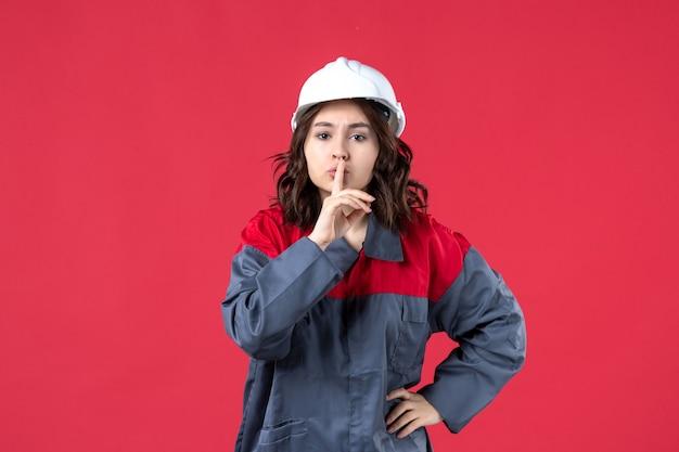Bovenaanzicht van vrouwelijke bouwer in uniform met harde hoed en stilte gebaar maken op geïsoleerde rode achtergrond