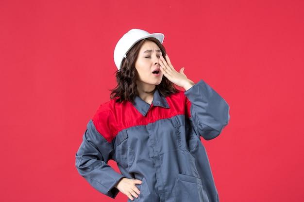 Bovenaanzicht van vrouwelijke bouwer in uniform met helm en geeuwen op geïsoleerde rode achtergrond