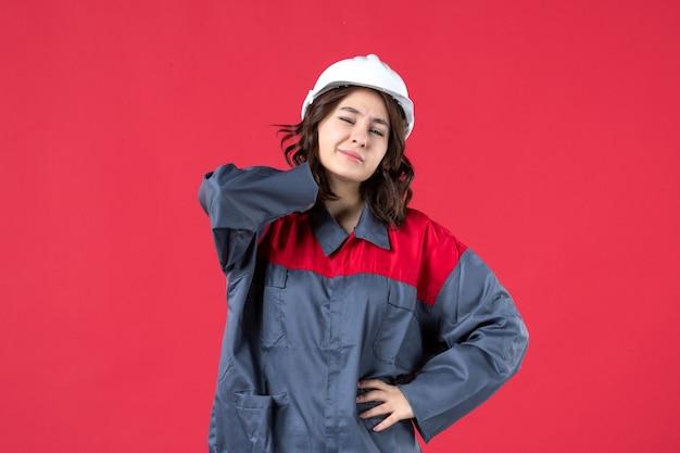 Bovenaanzicht van vrouwelijke bouwer in uniform met helm en leed aan hoofdpijn op geïsoleerde rode achtergrond