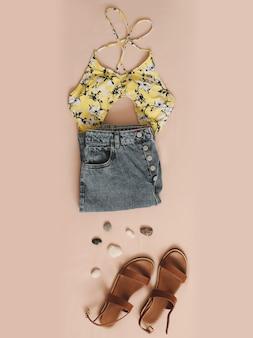Bovenaanzicht van vrouwelijke casual trendy zomeroutfit met badpak denim shorts en sandalen vakantie op se...