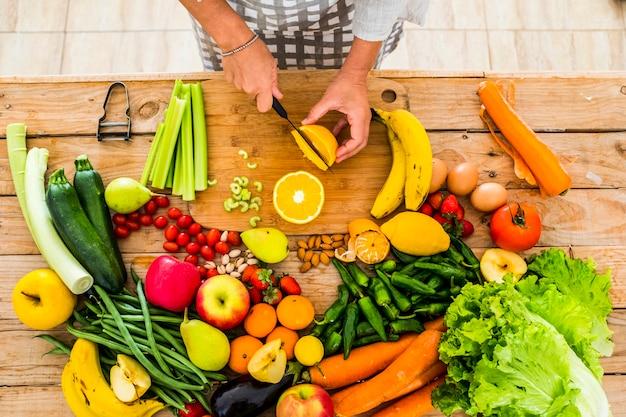 Bovenaanzicht van vrouwelijke chef-kok die gezonde natuurlijke voeding snijdt en bereidt op een houten tafel