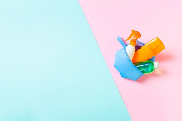 Bovenaanzicht van vrouwelijke cosmetica tas vol zonnebrandcrème spray, sunsreen, sunblock en bodylotion en spf crème op blauwe en roze achtergrond met kopieerruimte. recht boven. helder zomerconcept.