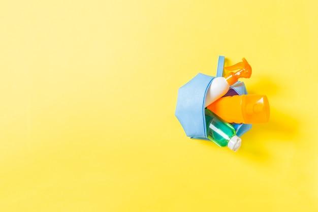 Bovenaanzicht van vrouwelijke cosmetica tas vol zonnebrandcrème spray, sunsreen, sunblock en bodylotion en spf crème op gele achtergrond met kopieerruimte. recht boven. helder zomerconcept.