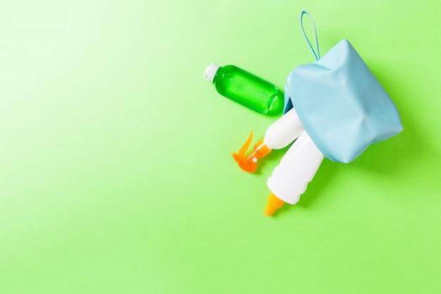 Bovenaanzicht van vrouwelijke cosmetica tas vol zonnebrandcrème spray, sunsreen, sunblock en bodylotion en spf crème op groene achtergrond met kopieerruimte. recht boven. helder zomerconcept.