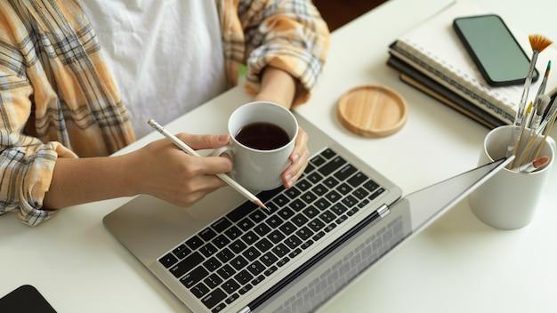 Bovenaanzicht van vrouwelijke freelancer handen met koffiekopje tijdens het werken met laptop op kantoor aan huis bureau