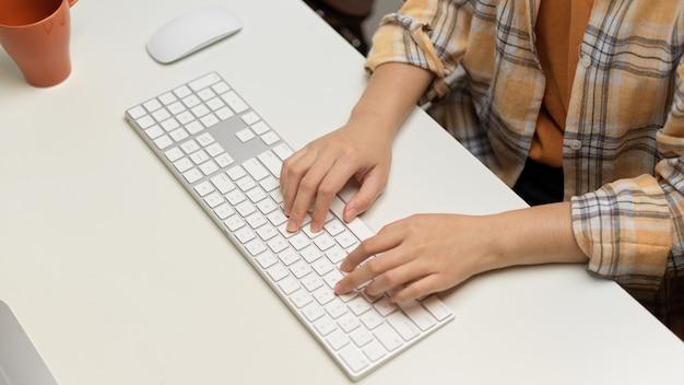 Bovenaanzicht van vrouwelijke freelancer handen typen op computertoetsenbord op witte tafel in kantoor aan huis kamer