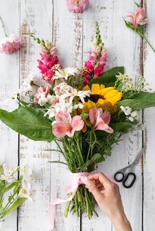 Bovenaanzicht van vrouwelijke hand die een boeket bloemen voorbereidt