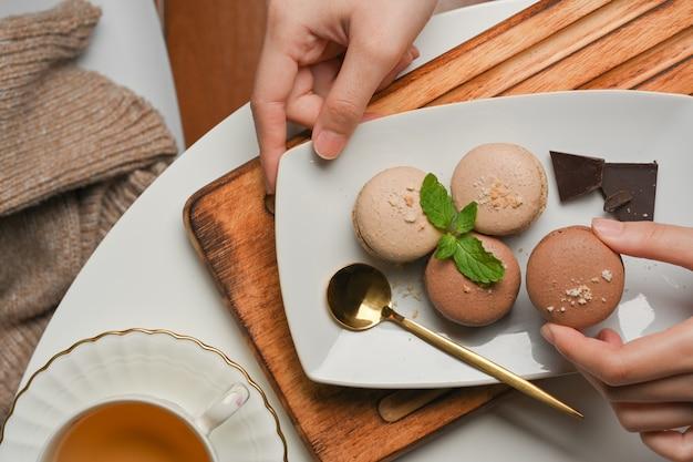Bovenaanzicht van vrouwelijke hand franse macarons plukken uit een plaat op koffietafel met kopje thee
