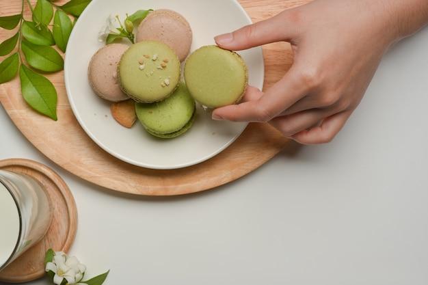 Bovenaanzicht van vrouwelijke hand franse macarons plukken uit een plaat op salontafel met melkglas