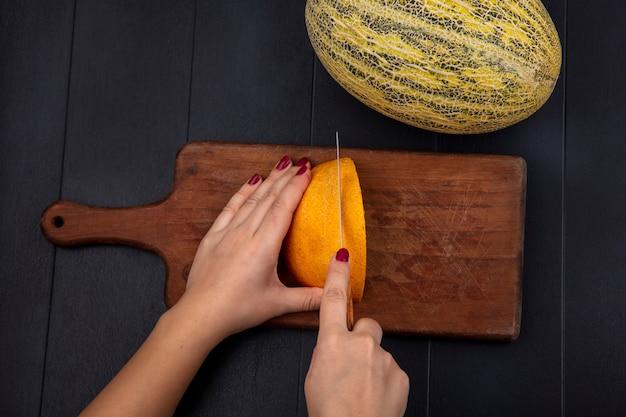Bovenaanzicht van vrouwelijke hand gele meloen snijden op houten keuken bord op zwart
