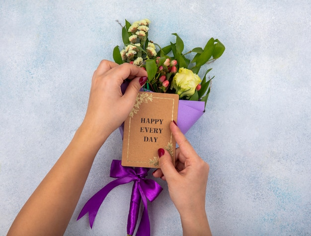 Bovenaanzicht van vrouwelijke hand met boeket van roos met bladeren en roze bessen op wit