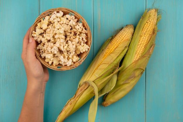 Bovenaanzicht van vrouwelijke hand met een emmer popcorn met verse likdoorns op een blauwe houten tafel
